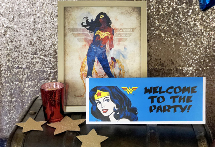 Wonder Woman images welcoming guests on top of suitcase to a Wonder Woman birthday party