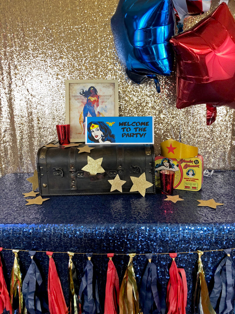 Suitcase on blue sequin tablecloth with gold stars and framed images for a Wonder Woman party
