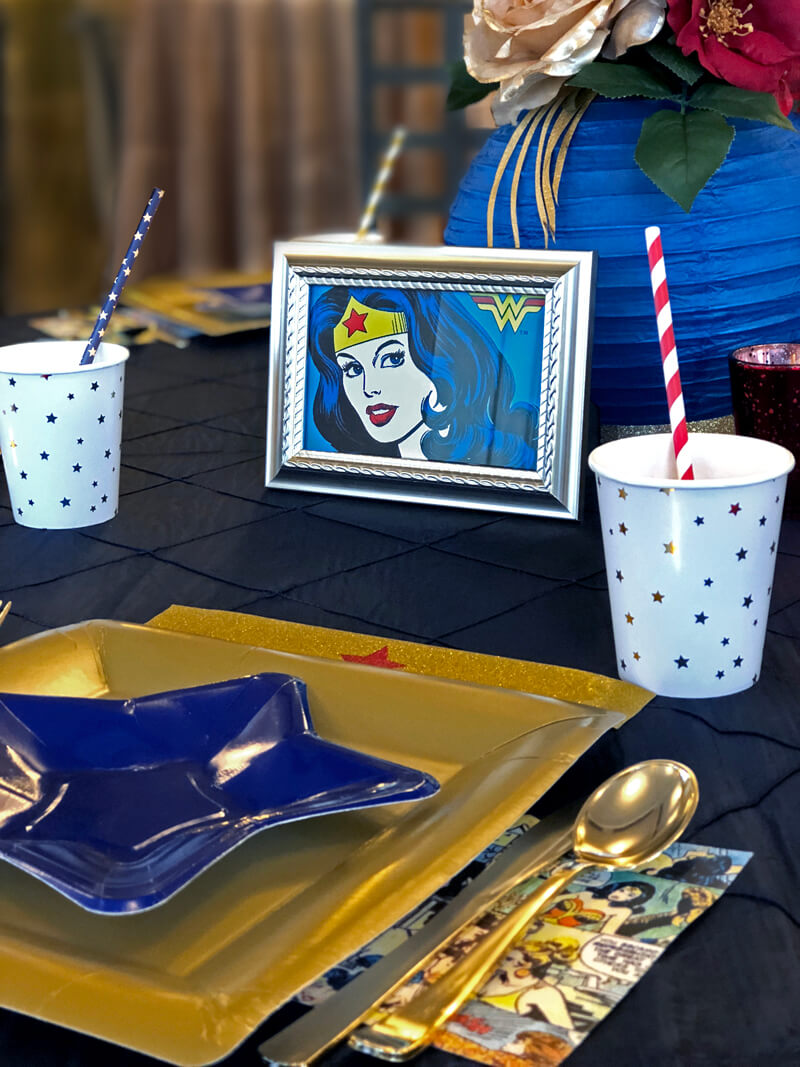 Gold plate with blue star dessert plate on navy blue tablecloth. Place setting for a Wonder Woman party