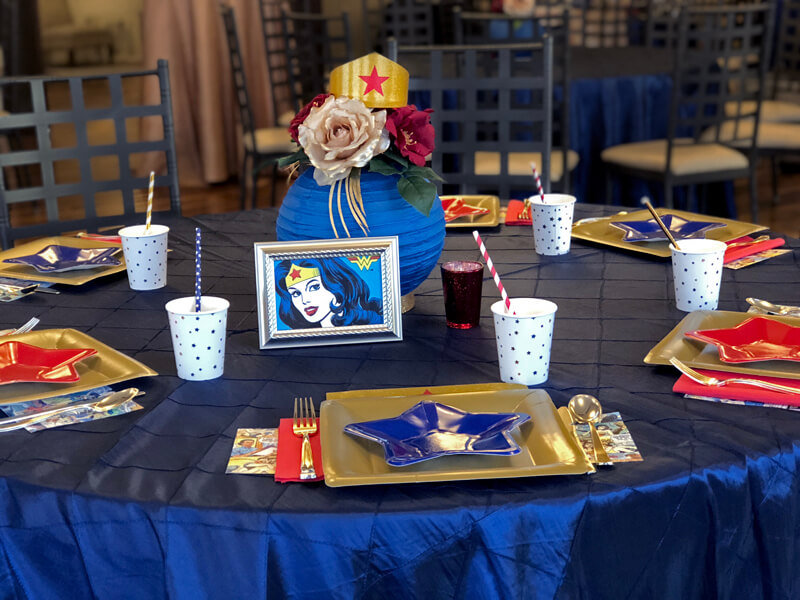 Table set with gold and star plates and floral lantern centerpiece for a Wonder Woman party