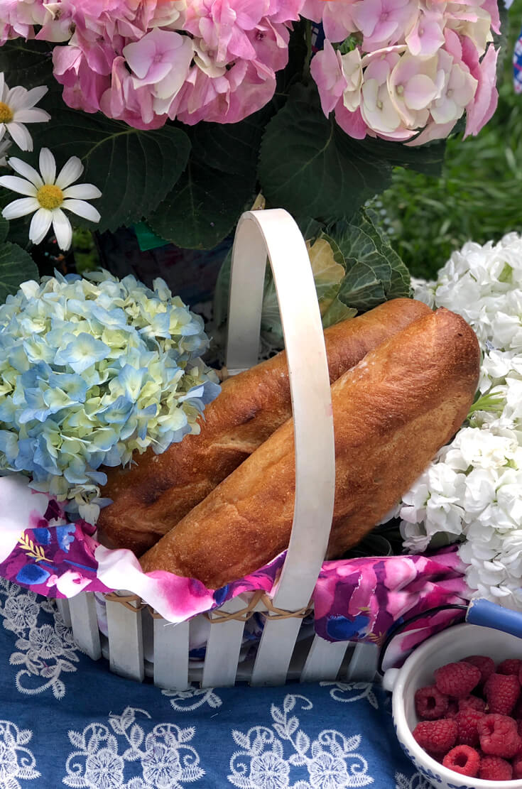 Basket with flowers and baguettes for summer picnic party