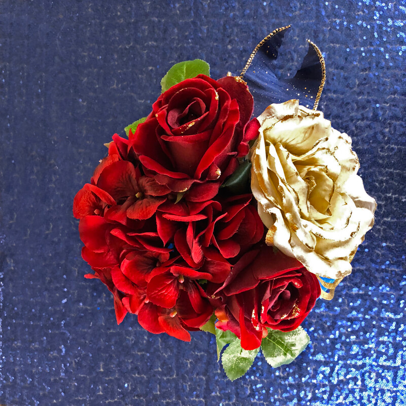 Red and gold flowers with blue ribbon in a floral lantern centerpiece.