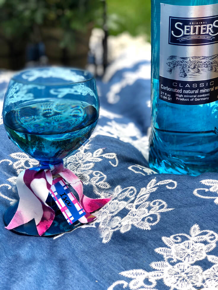 Cobalt blue glass and blue bottle of mineral water on blanket for charming summer picnic party