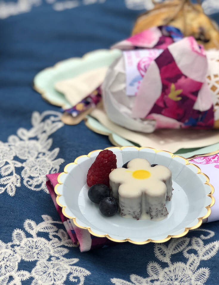 Plate of berries and chocolate flower treat on blanket for a charming summer picnic party