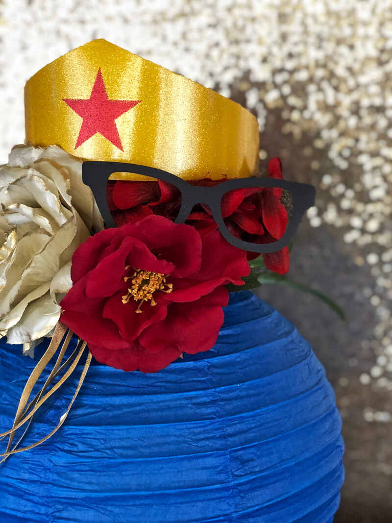 Paper eyeglasses and gold glitter crown in a Wonder Woman themed floral lantern centerpiece for a Wonder Woman party