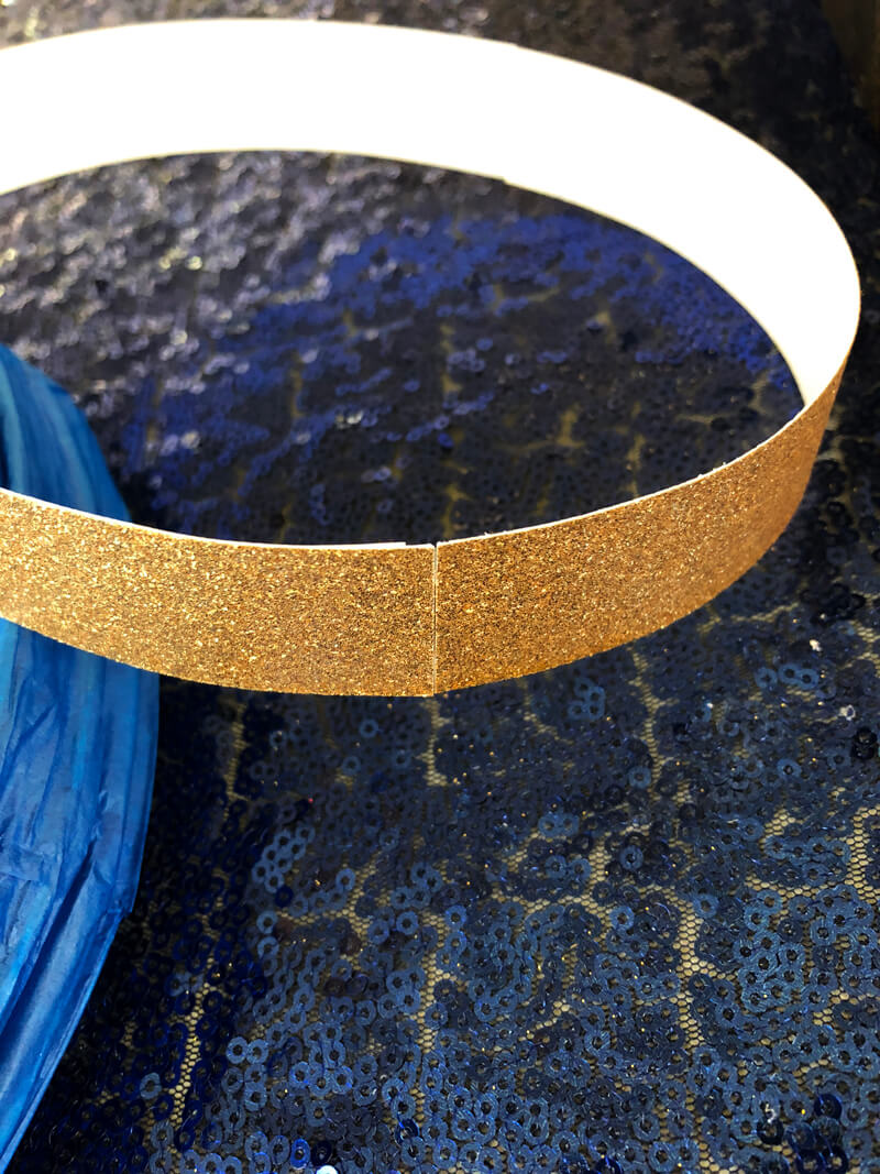 Gold glitter cardstock taped into a ring as the base for a floral lantern centerpiece.