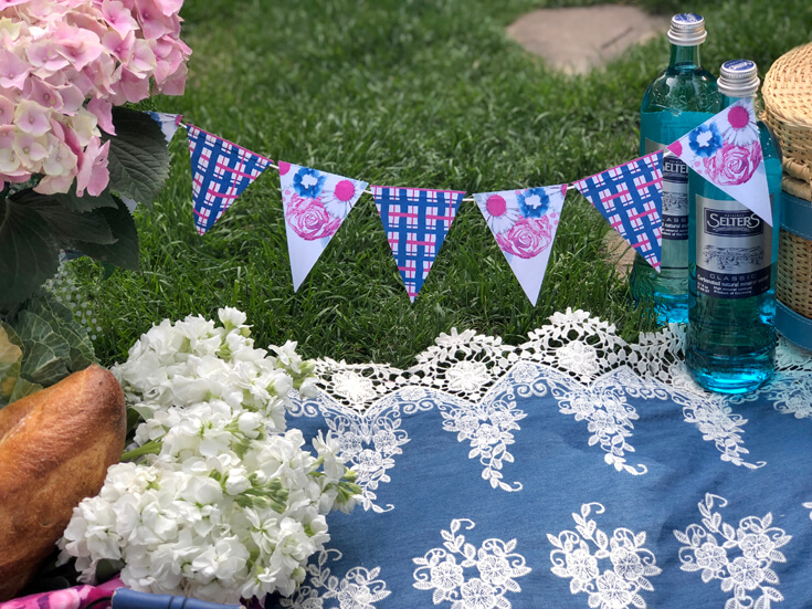 Mini pennant banner, blanket on grass for charming summer picnic party