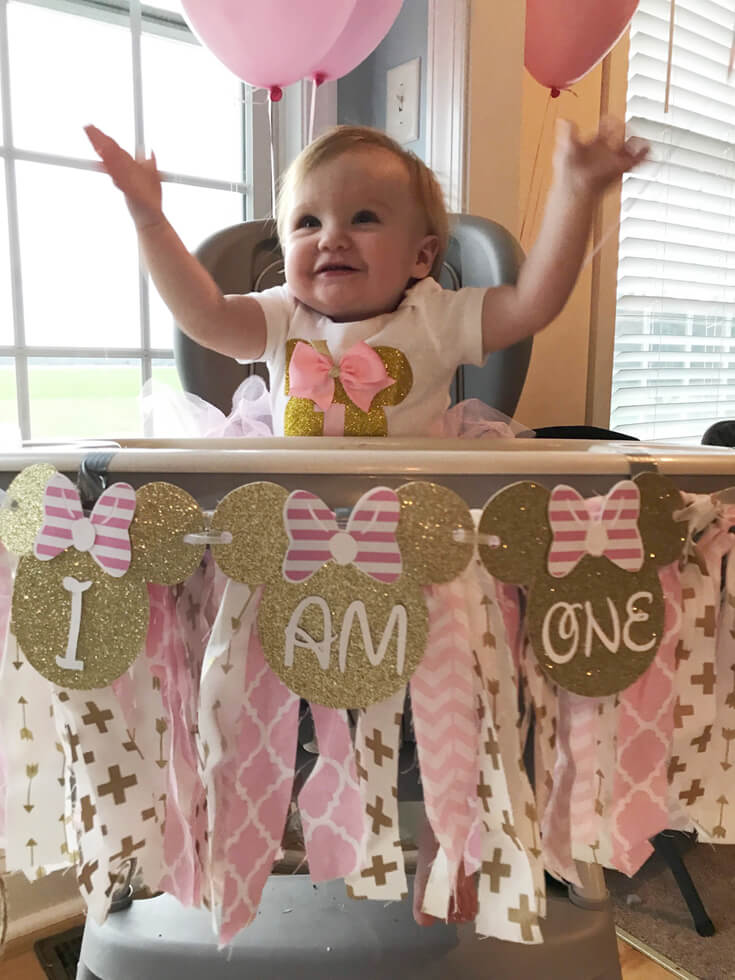 "Baby in high chair with banner ""I am one"" for Minnie Mouse first birthday party"