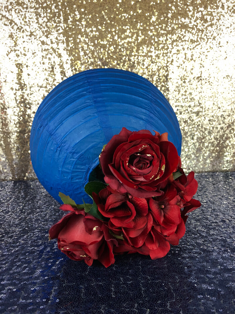 Blue paper lantern with red flowers on sequin table cover for a floral lantern centerpiece.