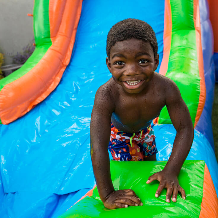 Boy at bottom of a bounce house water slide great for outdoor party games.
