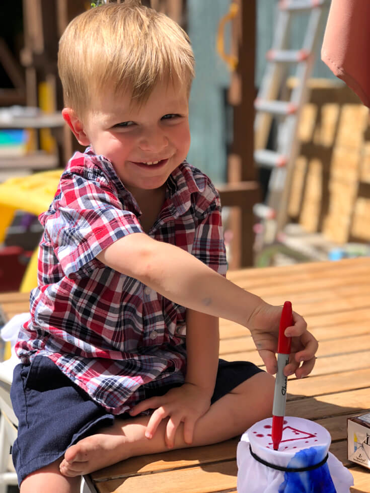 Boy proud of his sharpie shirt design for kid's party craft