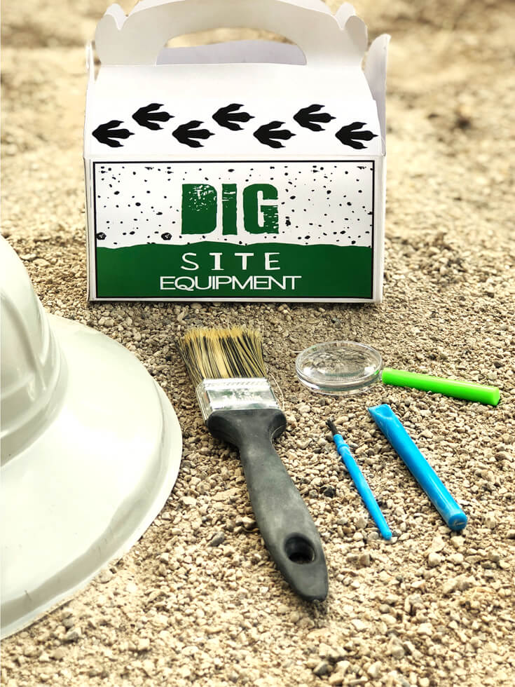 Dig site equipment box of paint brush, hat, magnifying glass, and chisel for a dino dig party activity