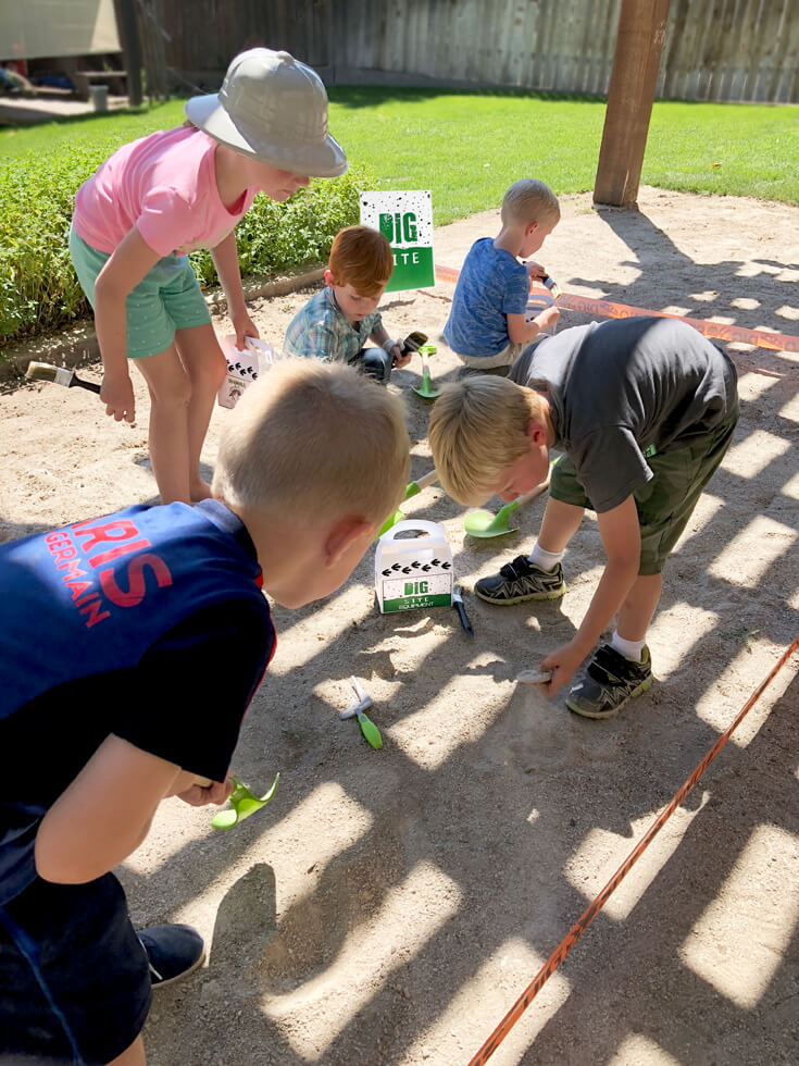 A group of budding paleontologists search for fossils at a dino dig party activity