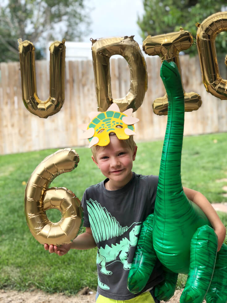 The birthday boy with dinosaur mask, inflatable brachiosaurus, and the number 6 balloon for for dinosaur birthday after a dino dig party activity