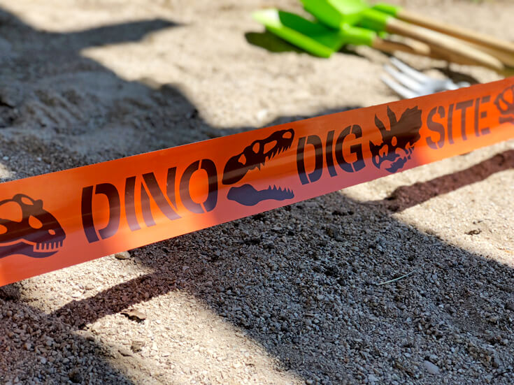 Orange dino dig site tape to cordon off the pit for a dino dig party activity