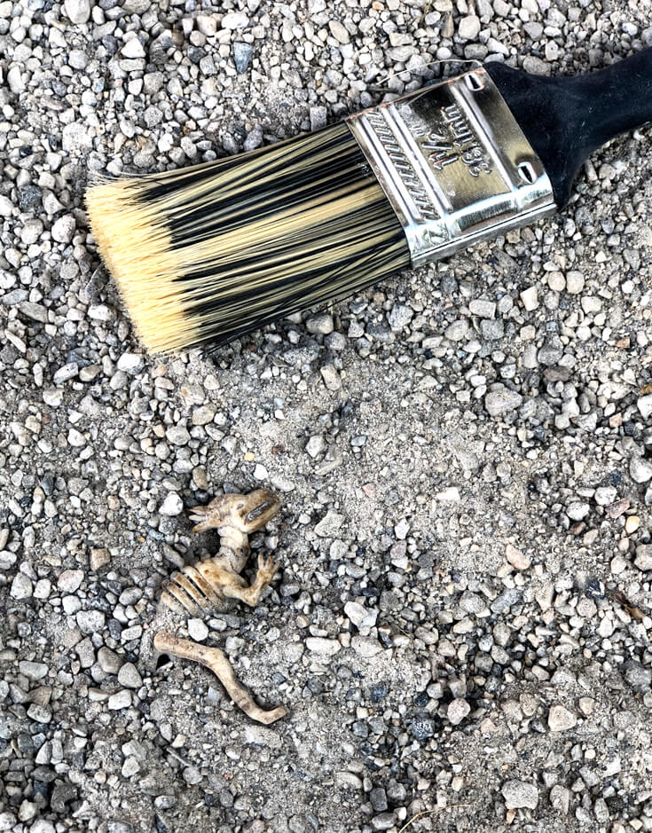 Toy dinosaur skeleton in the sand of a dino dig party activity site.