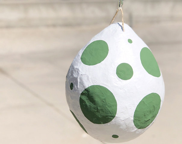 DIY Dino egg Piñata with bright green spots. The perfect dinosaur birthday party activity!