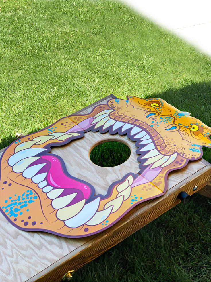 T-rex poster on a corn hole game makes for a fun feed the t-rex dinosaur party activity