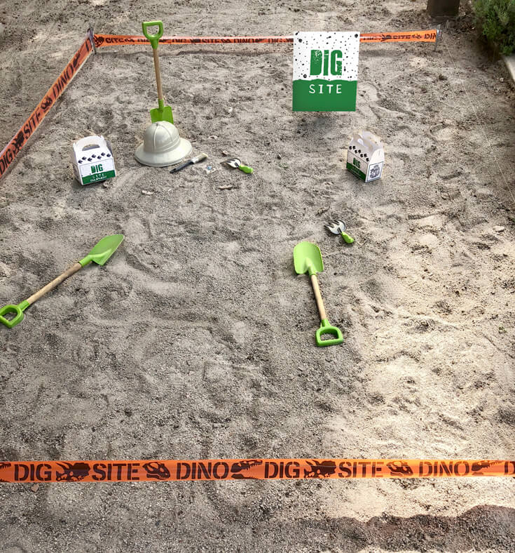 A sand pit cordoned off with tape to reveal a dino dig party activity