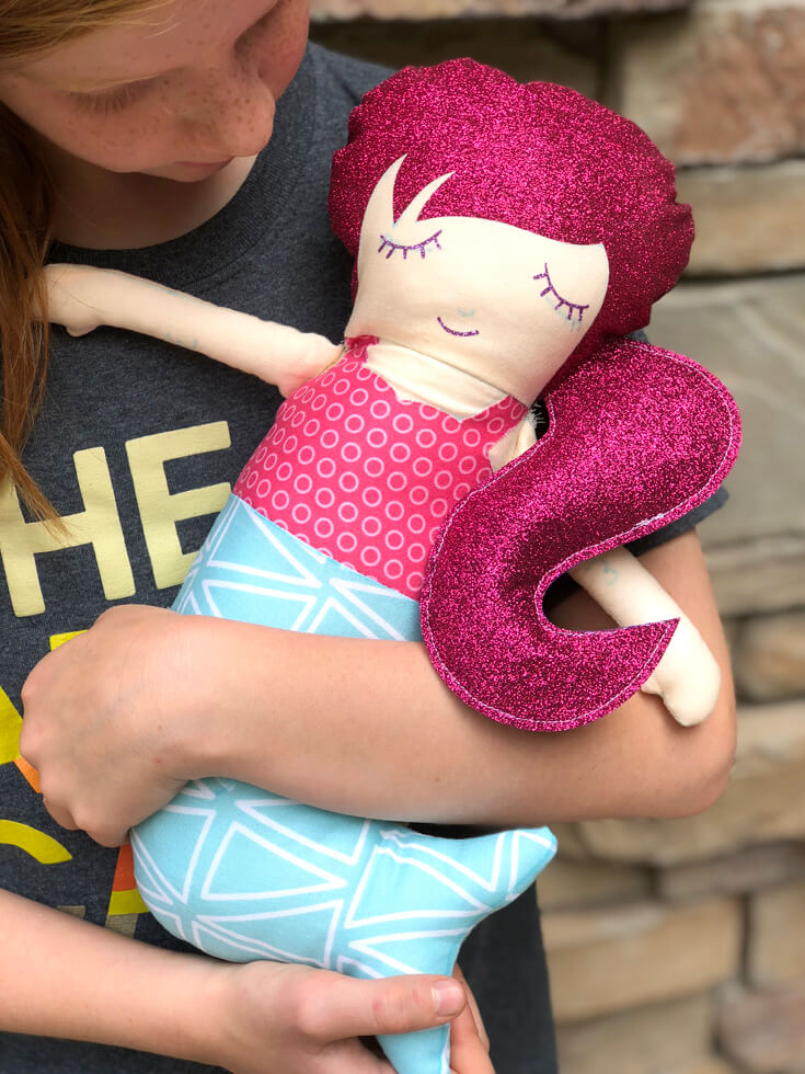 Girl holding a mermaid doll with pink glitter hair made at the Cricut Mountain Make-a-thon