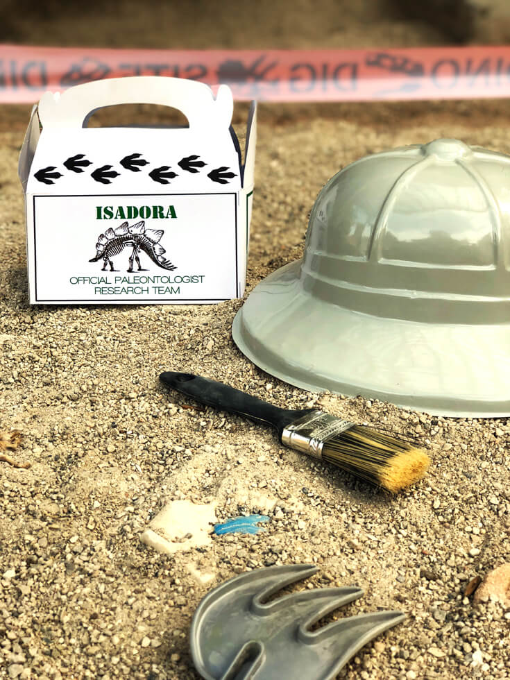 Dig site equipment box of paint brush, hat, and rake for a dino dig party activity