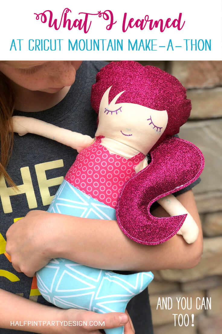 Little girl holding mermaid doll with pink glitter hair made at Cricut Mountain Make-a-thon