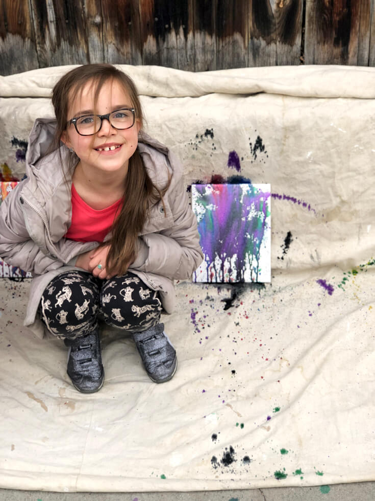 Little artist poses next to her work.