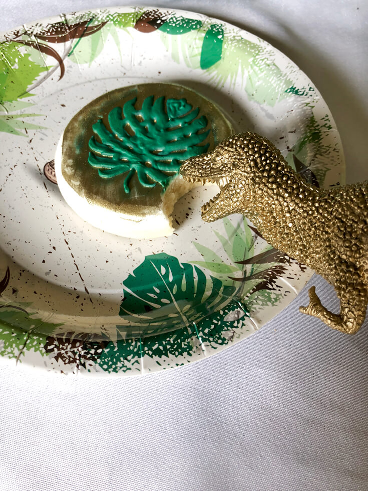 Gold dino eating a gold monstera leaf cookie at a dinosaur birthday party