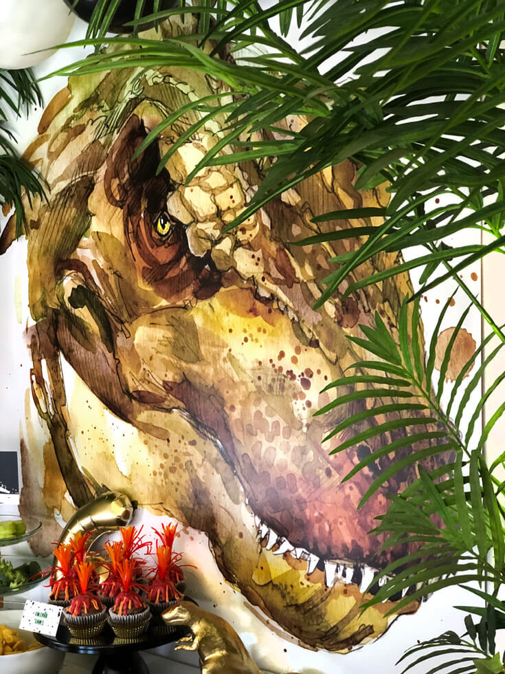 T-Rex graphic banner backdrop through the palms at a dinosaur birthday party