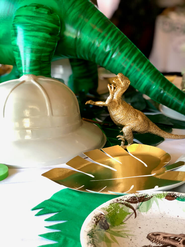 Gold dinos and monstera leaf plate with pith hat as place setting for a dinosaur birthday party
