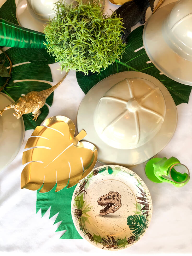 Gold monstera leaf plate, T-rex plate, green napkin with a bite, reptile cup, and pith hat for the perfect dinosaur birthday party place setting