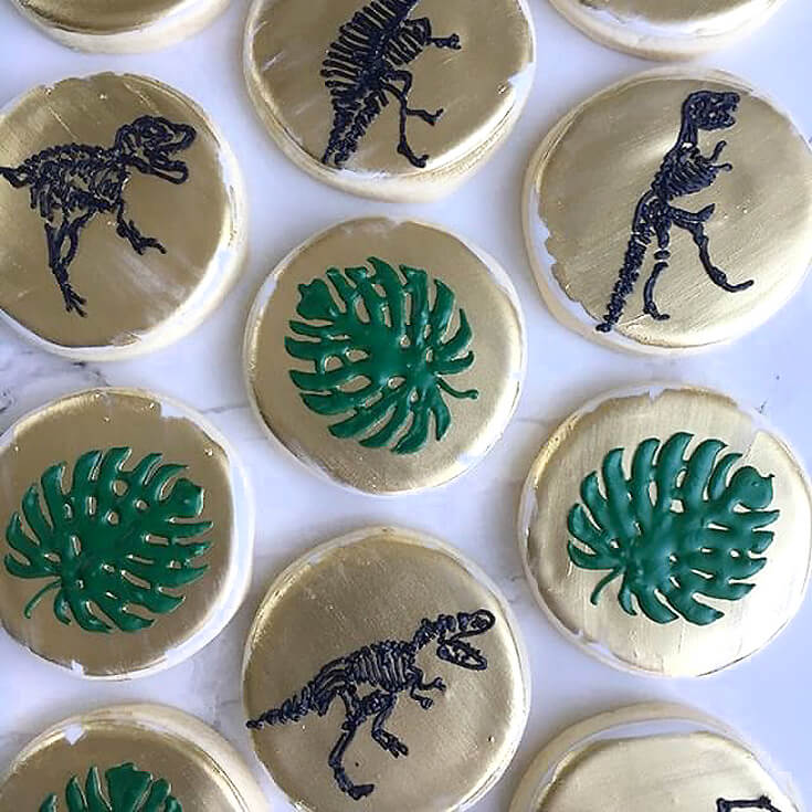 Monstera leaf and dinosaur fossil sugar cookies for a dinosaur birthday party idea.