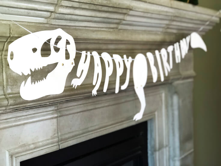 Happy birthday t-rex skeleton banner for a T-Rex inspired invitations with palm leaf background are a fun dinosaur birthday party