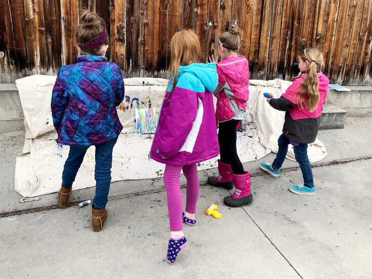 Keeping little artists busy. girls squirt gun painting on outdoor canvas