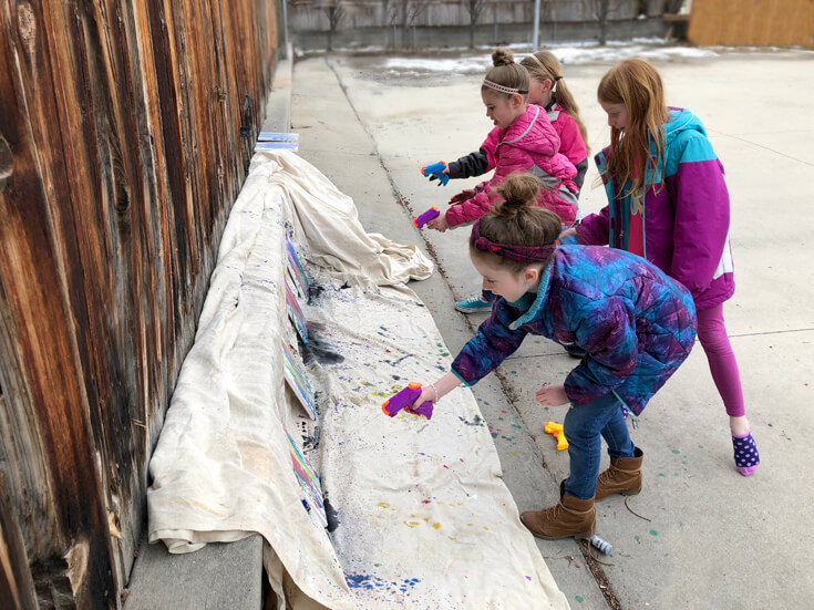Keeping little artists busy at an art party with squirt gun painting on outdoor canvases