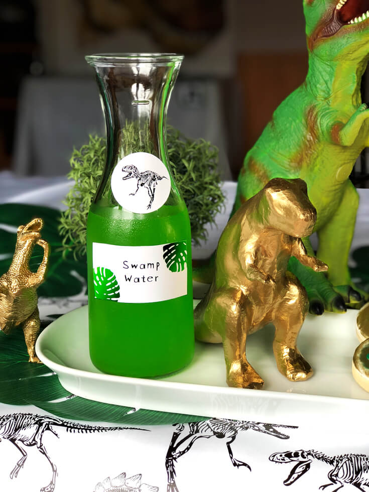 Green juice labeled Swamp water in a carafe is a fun dinosaur birthday party idea!