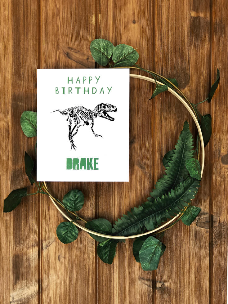 Happy Birthday sign on greenery wreath for a dinosaur birthday party welcome