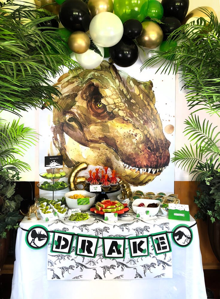 T-rex graphic backdrop, balloon garland, and potted palm trees are a fabulous dinosaur birthday party idea! And no licensed characters!