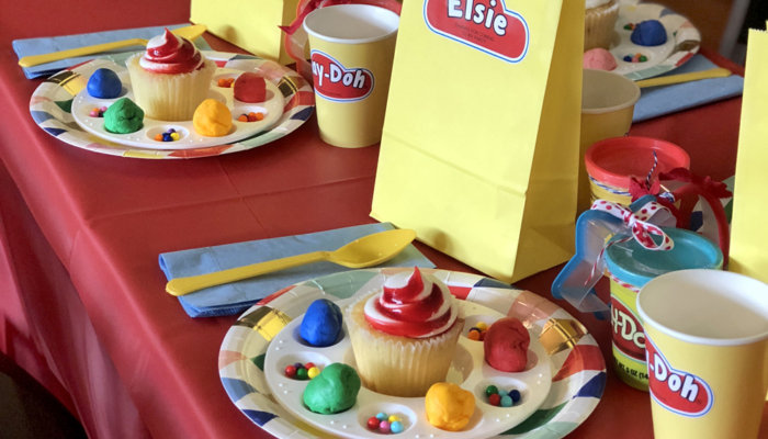Table set for a Play-doh birthday party with favor bags and cupcakes on colorful plates