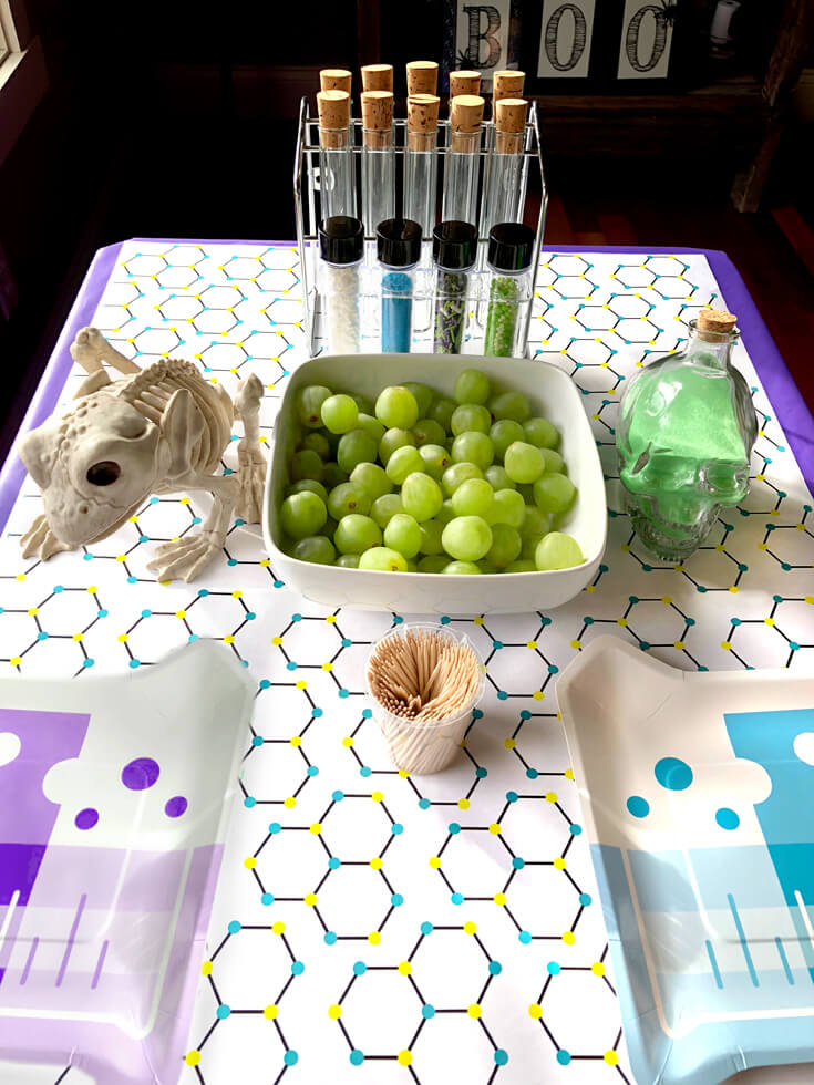 Science table set with grapes, toothpicks, beakers, and plates for a grape molecule food science activity