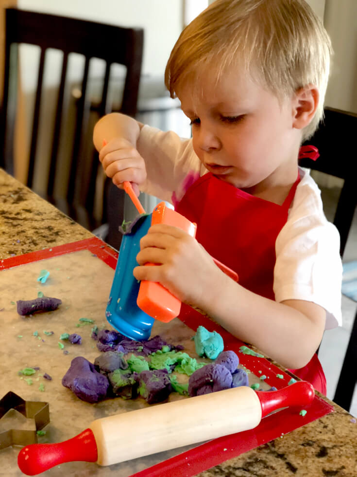 Child concentrating while working on an extruder with his playdough for a Play-doh birthday party