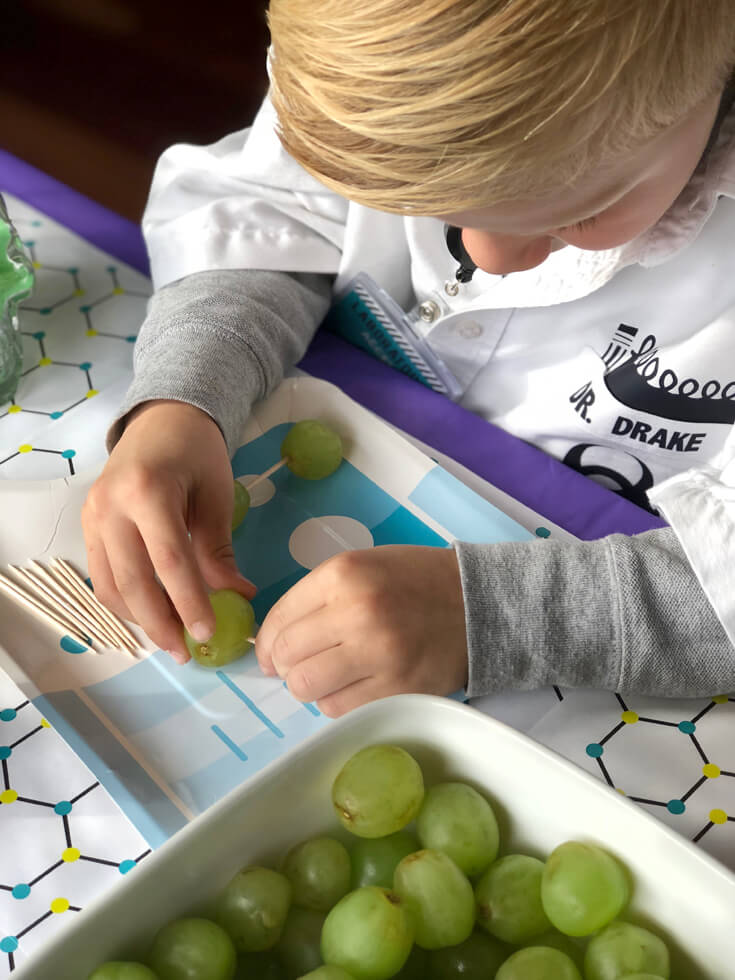 Boy concentrating on creating a grape molecule for food science activity