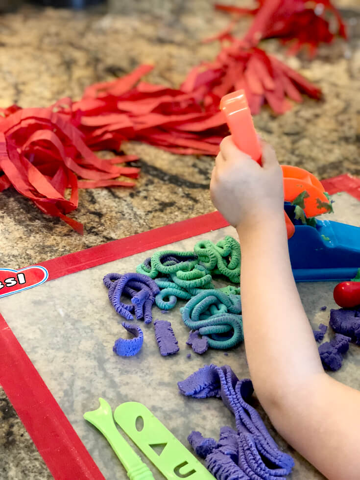 Child using an extruder to make playdough noodles at a Play-doh birthday party