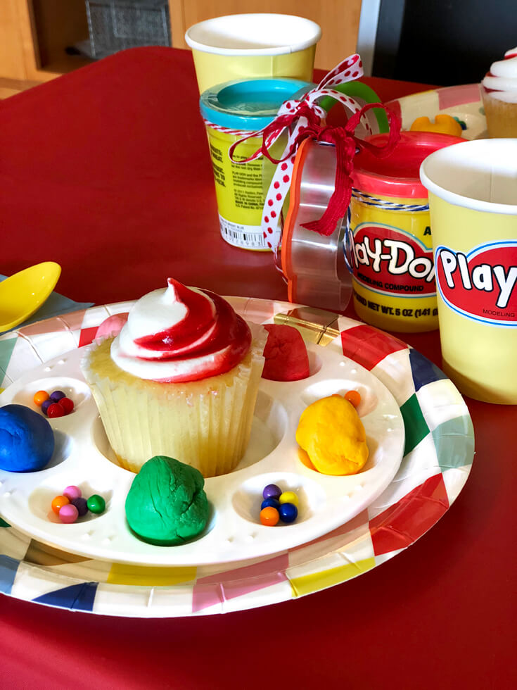 Colorful plate with cupcake and sprinkles with Play-doh party favor for a Play-doh birthday party
