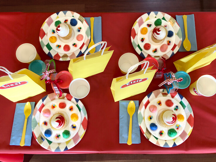 Party table with red table cover, colorful plates, cupcakes, and sprinkles for a Play-doh birthday party