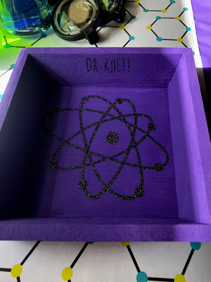 Swirly atom vinyl graphic on purple specimen tray - Mad Science Party Details with Cricut