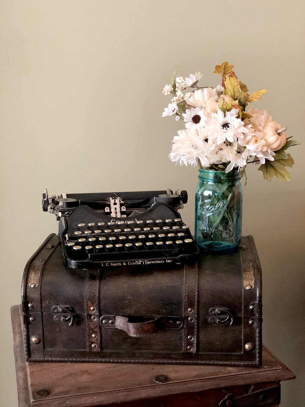 Vase of fall florals on suitcase with vintage typewriter for girls night harvest party decor ideas