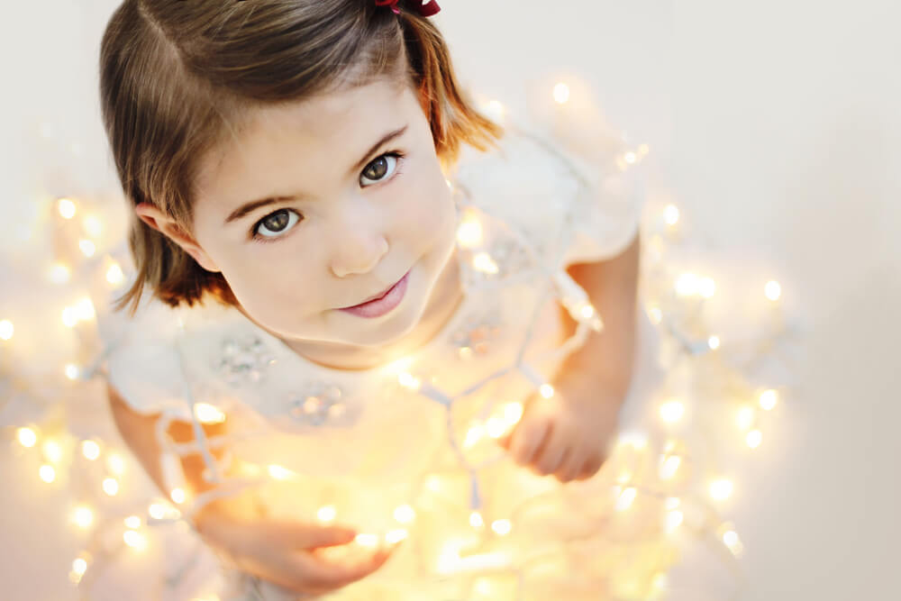 Girl with string lights, Light the World with service this Christmas