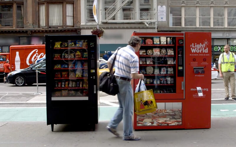 Man giving at a vending machine for the Light the World campaign