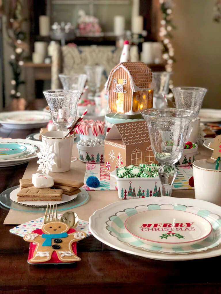 Table decorated with Gingerbread houses and candy for a Christmas Cookie Exchange Party